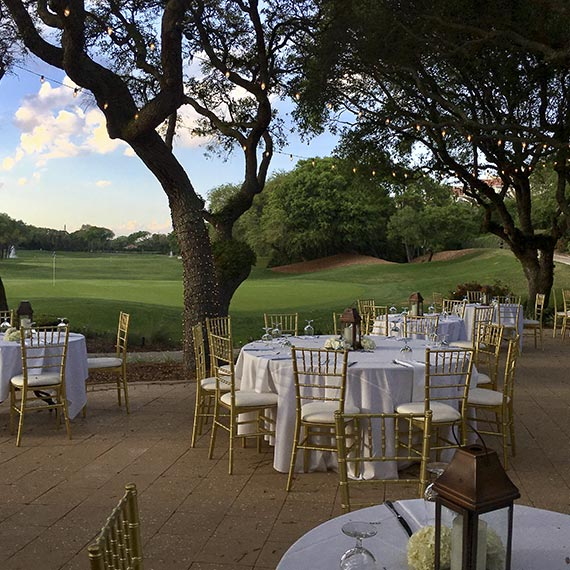 outdoor wedding set up, white tables and gold shairs over looking the golf course