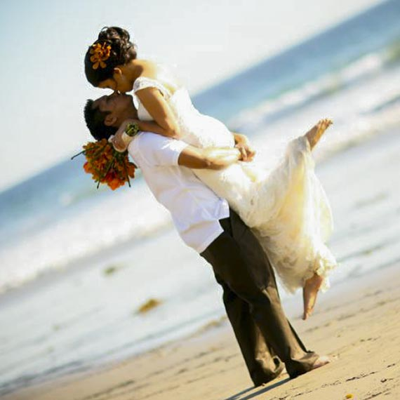 Young married couple kissing on beach