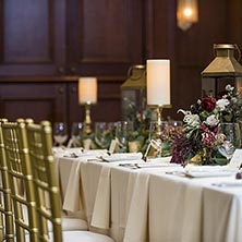 white tables and gold chairs with white candles