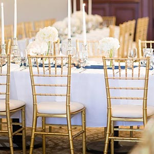 white table clothes and gold chairs with white flowers and candles