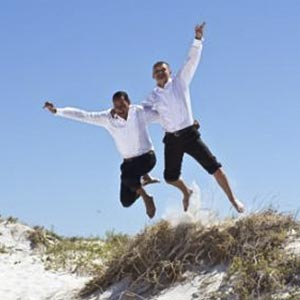 two men jumping off of beach mound