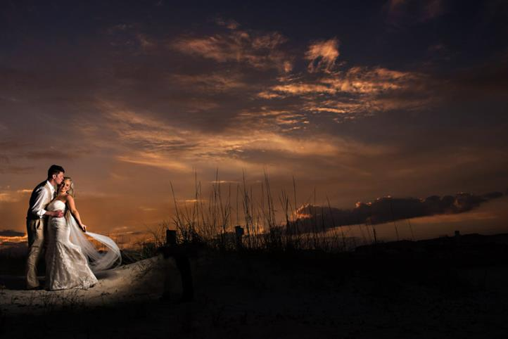 bride standing on the beach at sunset