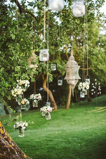 dainty flowers and tealight candles hanging from a tree