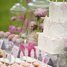 Three-layer wedding cake and desserts on table