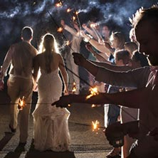 Young married couple walking through friends holding sparklers