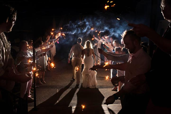 couple walking through crowd of sparklers