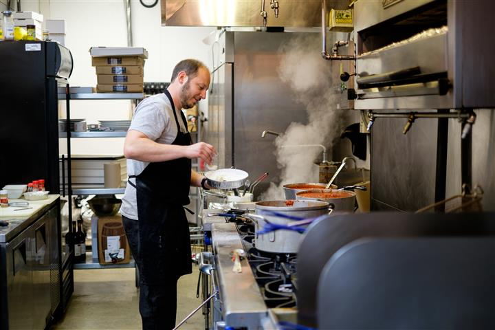 Man wearing apron in front of the stove cooking