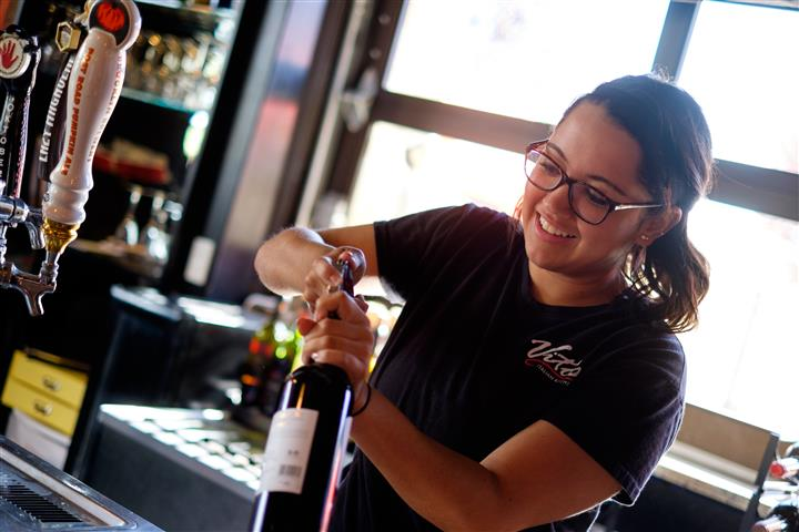 Server opening a bottle of wine behind the bar