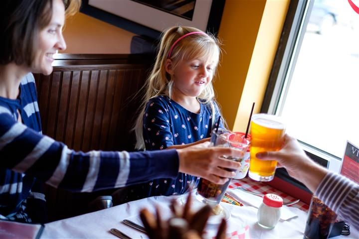 Young girl sitting at a booth in the restaurant raising their glasses to toast