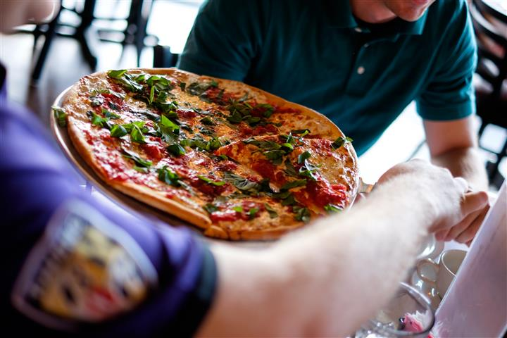 Close up of a pizza being served at the table