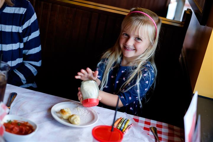 Little girl eating and smiling for a photo at the table