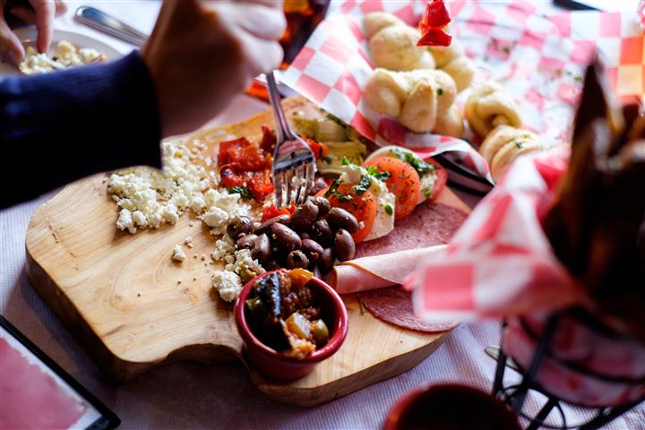 Wooden board with a variety of deli snacks served on the table