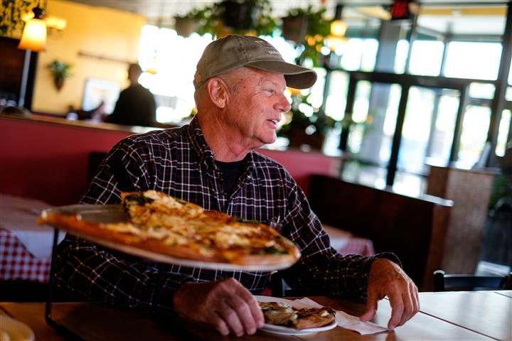 Man sitting at the table with a tray of pizza being served