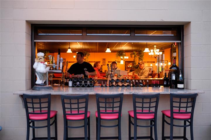 Photo of the outside bar with the stools and the bar tender behind it