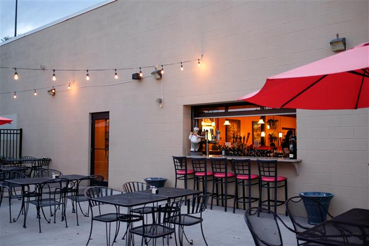 Exterior photo of the bar from the patio with red umbrellas