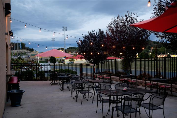 Restaurant patio vie with tables and red umbrellas decorated with string lights