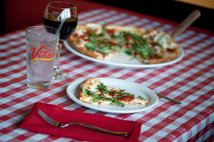 Table with a pizza derved in a tray and a plate with a pizza slice and drinks in the background