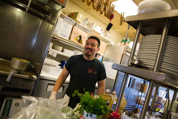 Man standing in the restaurant kitchen smiling for photo