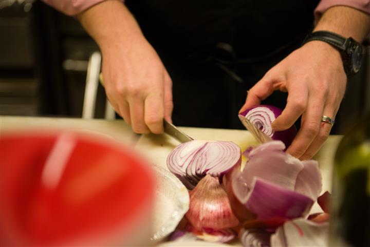 Close up photo of someone cutting up red onions