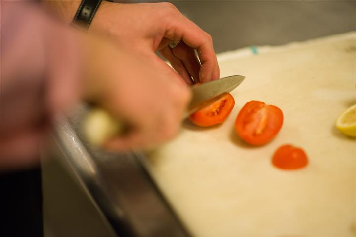 Close up photo of someone cutting up a a tomato to wedges
