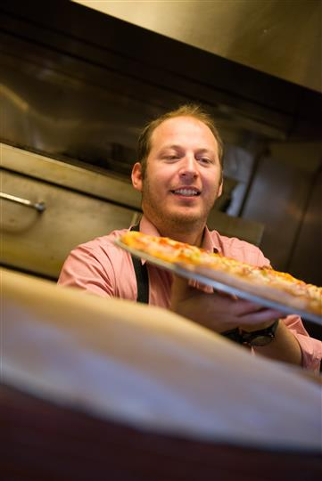 Man wearing an apron handing over a tray of pizza to someone