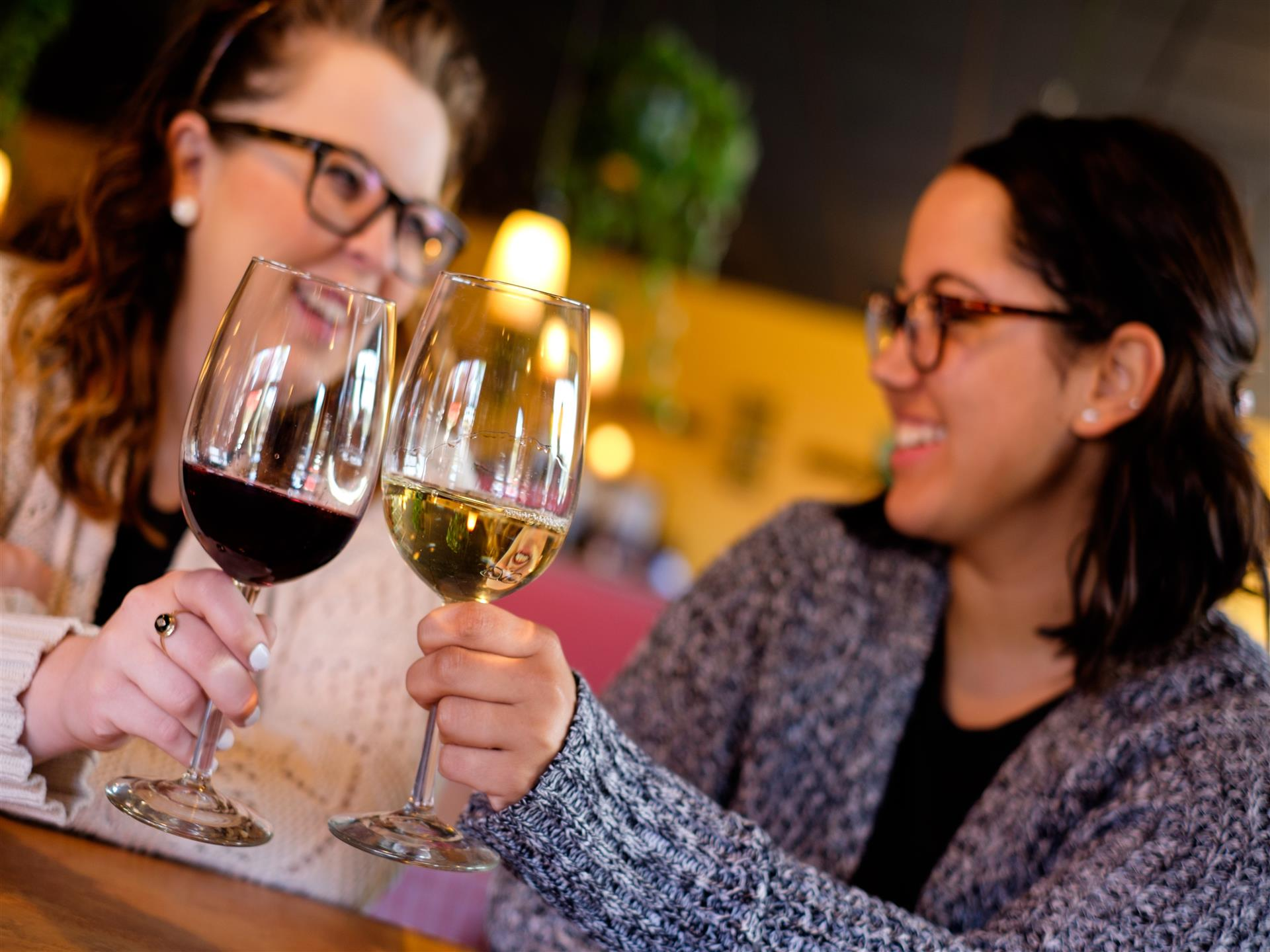 Two women cheersing two glasses of red and white wine