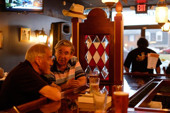 Bar with two men talking to each other