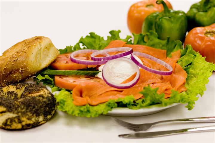 Lox platter with bagels, tomatoes, onions over bed of lettuce.