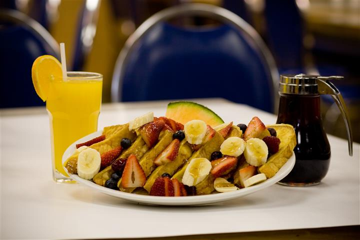 French toast with bananas, strawberries, blueberries and cantaloupe on dish with side of syrup and glass of O J