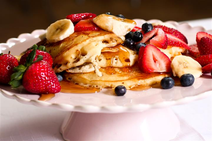 Pancakes with bananas, blueberries, strawberries and syrup
