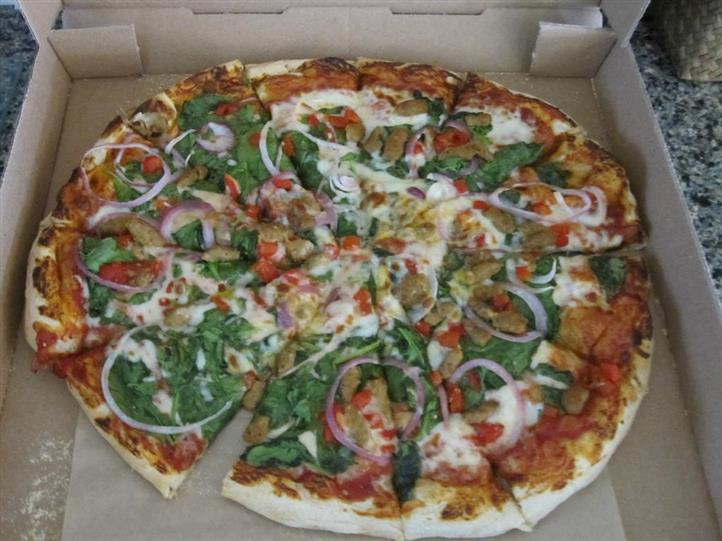Pizza cut into slices layered with various vegetables