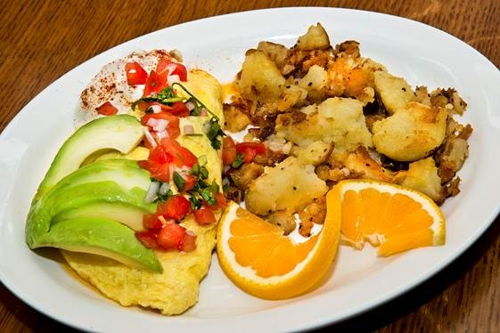 omelete layered with tomatoes and avocado and a side oh home fried garnished with an orange