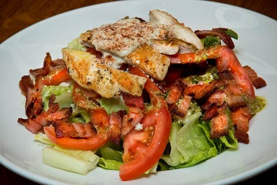 Grilled chicken over bed of greens with tomatoes, bacon and dressing