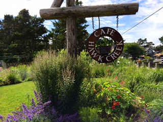 Cafe Hawk Creek wooden sign outdoors next to flowers and shrubs