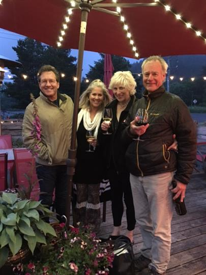 Group of people holding glasses of wine on patio