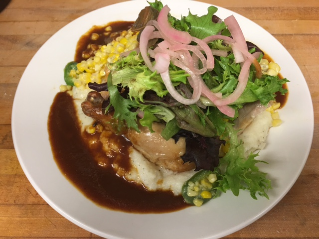 Chicken and mashed potatoes dish layered with field greens and topped with onions