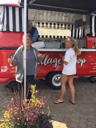 Two women smiling in front of Village Scoop food truck