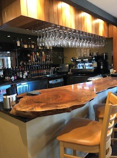 Bar stocked with liqour and wine with a wooden tabletop bar counter