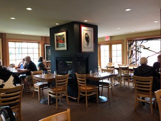 Inside of the Cafe On Hawk Creek. Tables and chairs and a fireplace in the middle of the room.