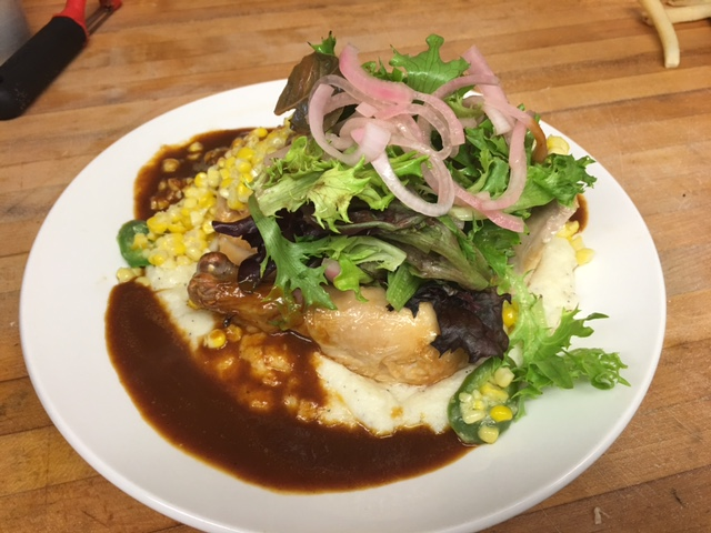 Roasted chicken on a pile of mashed potatoes with corn and topped with lettuce and pickled onions.