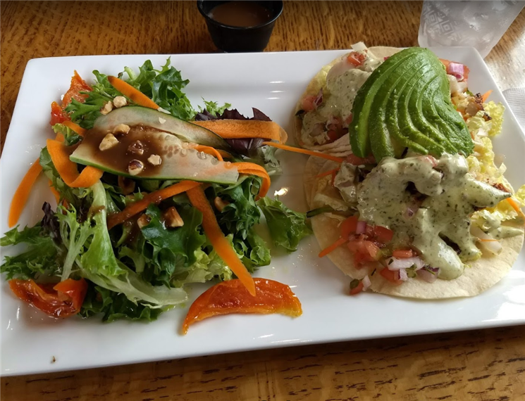 soft tacos with avocado, tomatoes, and a sauce next to a house salad with peppers, carrots, romaine lettuce, and cucumber drizzled with balsamic dressing.