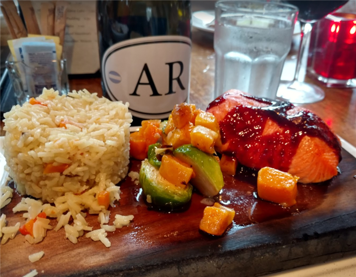 Salmon topped with a glaze.  Roasted vegetables of sweet potatoes and brussel sprouts next to fried vegetable rice.