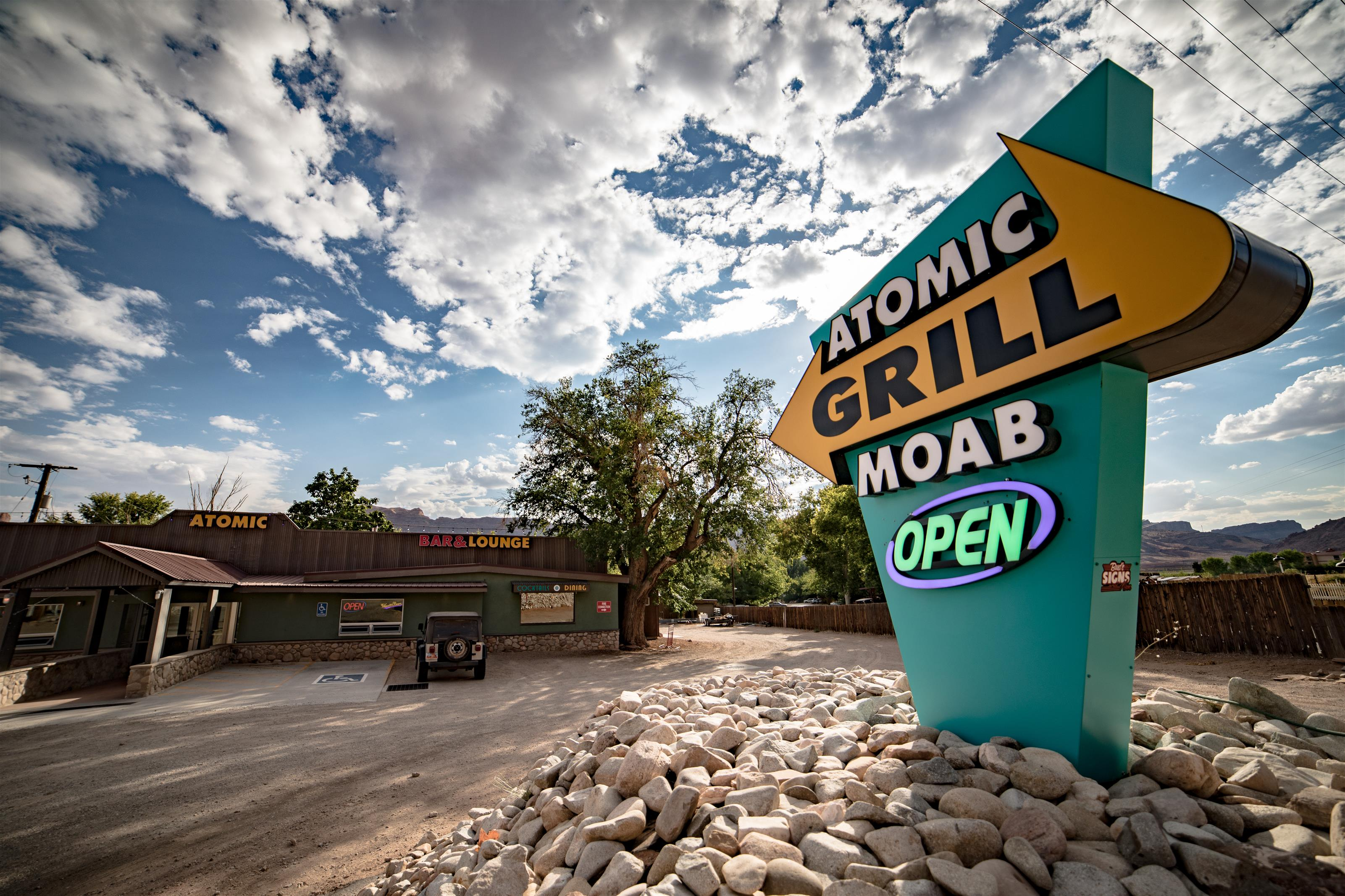 """Atomic Grill Moab"" sign with establishment in the background"