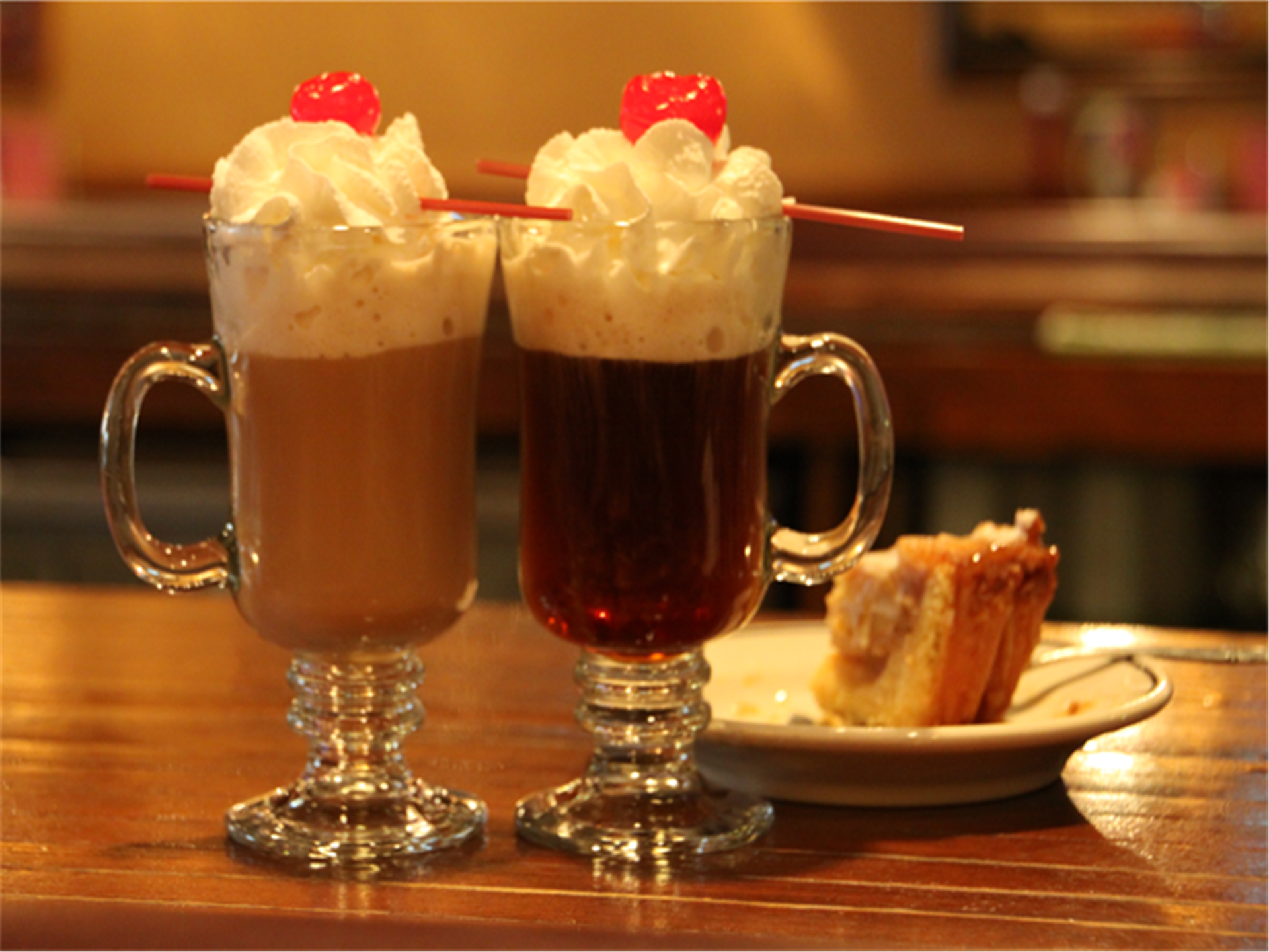 two milkshakes topped with whipped cream and cherries with a piece of cake on a table