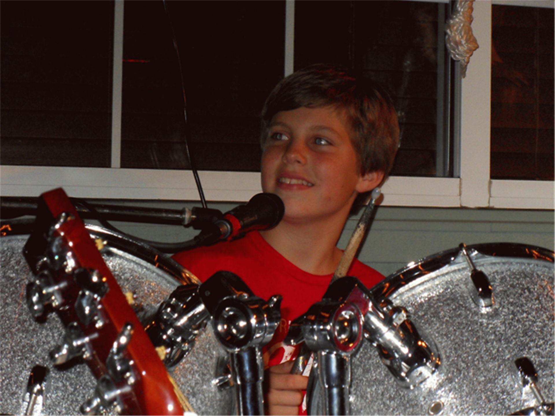 young boy sitting behind drum set
