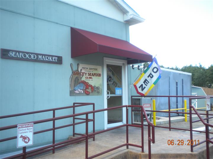 outside view of restaurant with flag that says open
