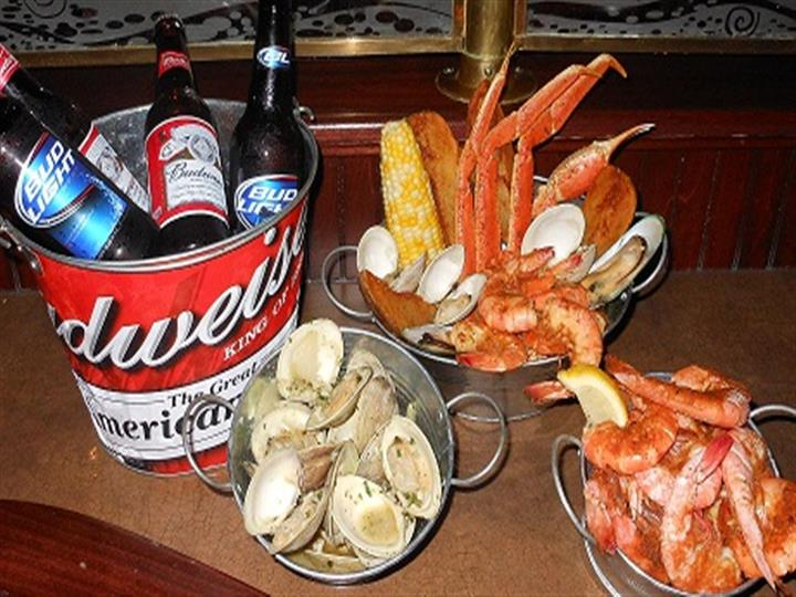 crab legs, oysters, shrimp, assorted beer in a bucket