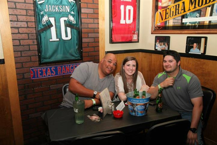 Two men and a woman sitting at a table with a bucket of beers.