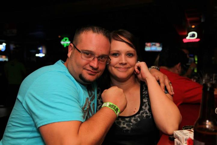 Man with his arm around a woman's shoulder posing for the camera.