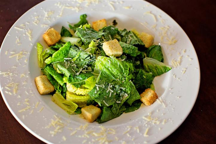 Caesar salad with parmesan cheese and croutons in a white bowl.